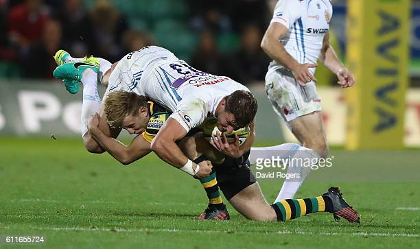 Ollie Devoto of Exeter is tackled by Sam Olver during the Aviva Premiership match between Northampton Saints and Exeter Chiefs at Franklin's Gardens...