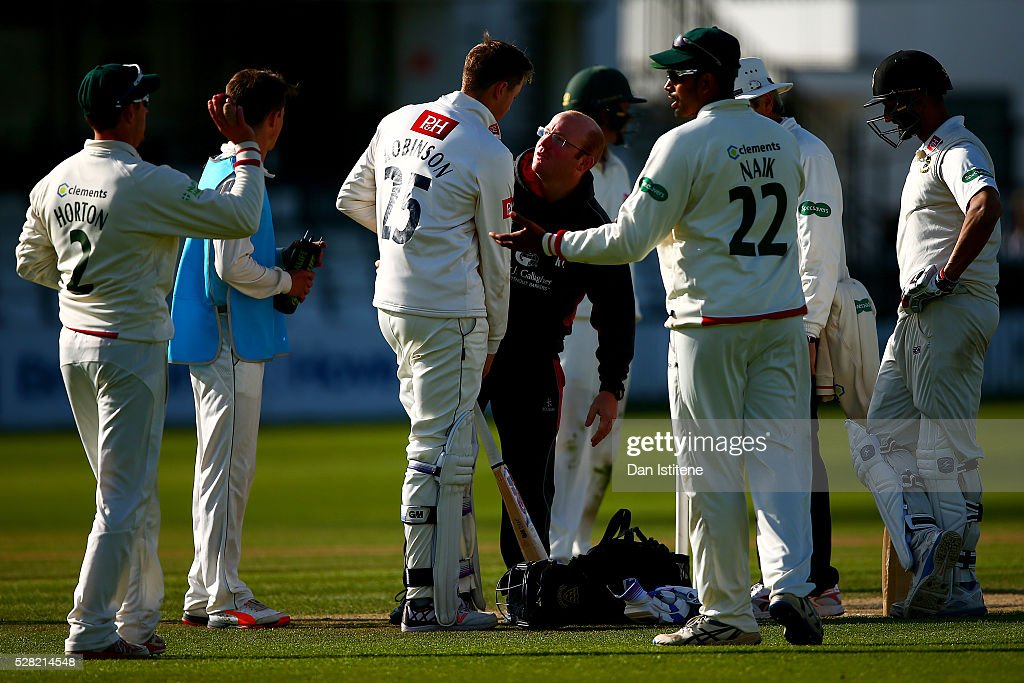 Ollie Robinson of Sussex is assisted by medical staff after being struck on the helmet by a delivery during the Specsavers County Championship Division Two match between Sussex and Leicestershire at The 1st Central County Ground on May 4, 2016 in Hove, England.