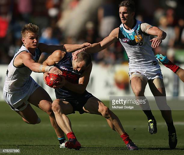 Ollie Wines and Hamish Hartlett of the Power tackle Daniel Cross of the Demons during the round nine AFL match between the Melbourne Demons and the...