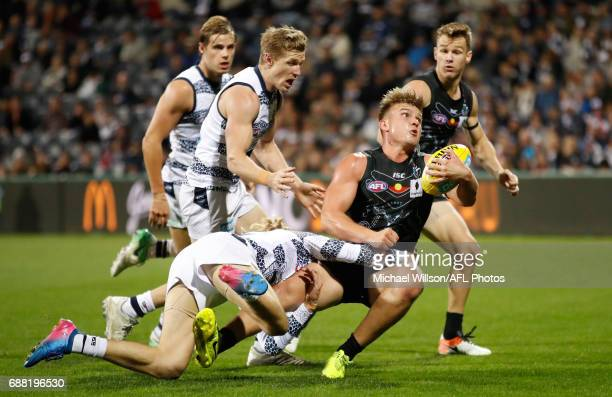 Ollie Wines of the Power is tackled by Cameron Guthrie of the Cats during the 2017 AFL round 10 match between the Geelong Cats and Port Adelaide...