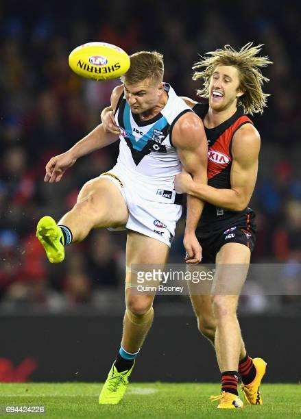 Ollie Wines of the Power kicks whilst being tackled Dyson Heppell of the Bombers during the round 12 AFL match between the Essendon Bombers and the...