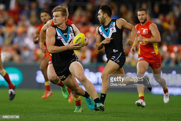 Ollie Wines of the Power runs the ball during the round 23 AFL match between the Gold Coast Suns and the Port Adelaide Power at Metricon Stadium on...