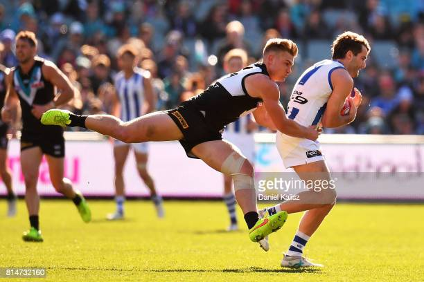Ollie Wines of the Power tackled Luke McDonald of the Kangaroos during the round 17 AFL match between the Port Adelaide Power and the North Melbourne...
