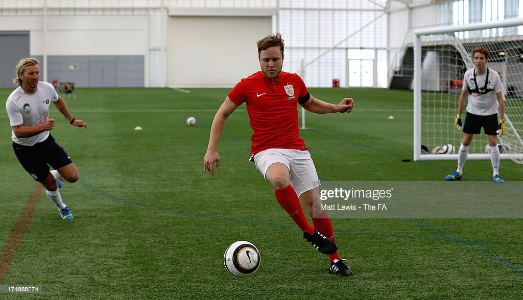 <a gi-track='captionPersonalityLinkClicked' href=/galleries/search?phrase=Olly+Murs&family=editorial&specificpeople=6350751 ng-click='$event.stopPropagation()'>Olly Murs</a> of Team Murs (C) controls the ball, marked by <a gi-track='captionPersonalityLinkClicked' href=/galleries/search?phrase=Robbie+Savage&family=editorial&specificpeople=169889 ng-click='$event.stopPropagation()'>Robbie Savage</a> (L) and <a gi-track='captionPersonalityLinkClicked' href=/galleries/search?phrase=Nick+Grimshaw&family=editorial&specificpeople=4666727 ng-click='$event.stopPropagation()'>Nick Grimshaw</a> (R) of Team Grimshaw during the BBC Radio 1 five-a-side football match between Team Grimshaw, captained by BBC Radio 1 DJ <a gi-track='captionPersonalityLinkClicked' href=/galleries/search?phrase=Nick+Grimshaw&family=editorial&specificpeople=4666727 ng-click='$event.stopPropagation()'>Nick Grimshaw</a> and Team Murs, captained by singer and FA150 ambassador <a gi-track='captionPersonalityLinkClicked' href=/galleries/search?phrase=Olly+Murs&family=editorial&specificpeople=6350751 ng-click='$event.stopPropagation()'>Olly Murs</a>, at St Georges Park on July 29, 2013 in Burton-upon-Trent, England. In the build-up to Sir Bobby Robson National Football Day on August 10, the 5-a-side match was one of many events taking place around the country to mark The FA's 150th anniversary.