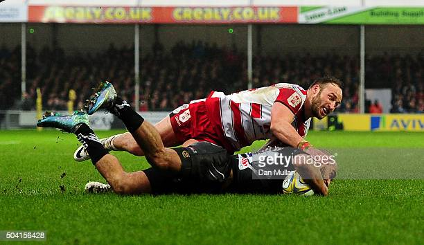 Olly Woodburn of Exeter Chiefs dives over for his side's third try as he is tackled by Bill Meakes of Gloucester during the Aviva Premiership match...