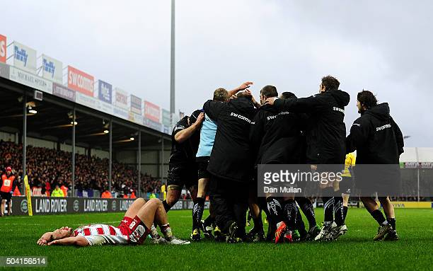 Olly Woodburn of Exeter Chiefs id mobbed by his team mates after scoring their third try as Bill Meakes of Gloucester lies dejected during the Aviva...