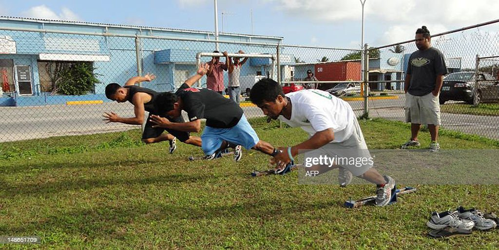 Oly-2012-athletics-Marshalls,FEATURE by Giff Johnson This undated photo received on June 27, 2012 shows Marshall Islander Timi Garstang (L) with other sprinters practicing on a grass field in Majuro in preparation for the London Olympic Games. When Marshall Islands sprinter Timi Garstang steps into London's Olympic Stadium, he will be in a facility that holds 30,000 more people than the entire population of his Pacific nation. AFP PHOTO / Giff Johnson