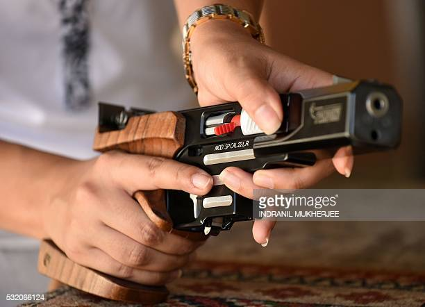 WITH 'OLY2016INDshooting' INTERVIEW by Peter HUTCHISON In this photograph taken on April 25 Indian shooter Heena Sidhu prepares a pistol before...