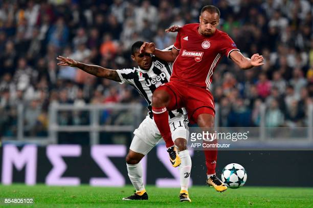 Olympiacos' Belgian midfielder Vadis Odjida Ofoe fights for the ball with Juventus' forward from Brazil Douglas Costa during the UEFA Champion's...
