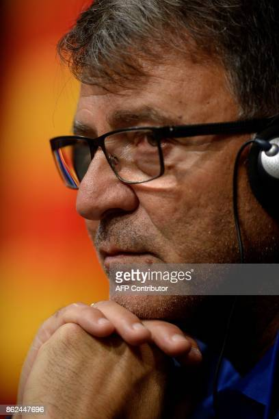 Olympiacos' head coach Takis Lemonis looks on during a press conference at the Camp Nou staduium in Barcelona on October 17 2017 on the eve of the...