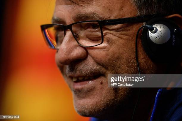 Olympiacos' head coach Takis Lemonis smiles during a press conference at the Camp Nou staduium in Barcelona on October 17 2017 on the eve of the UEFA...