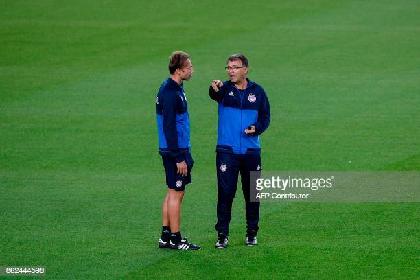 Olympiacos' head coach Takis Lemonis speaks with his assistant during a training session at the Camp Nou stadium in Barcelona on October 17 2017 on...