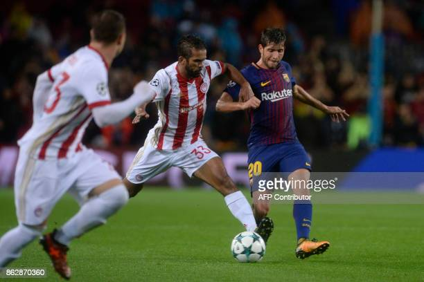 Olympiacos' Moroccan midfielder Mehdi CarcelaGonzalez vies with Barcelona's Spanish midfielder Sergi Roberto during the UEFA Champions League group D...