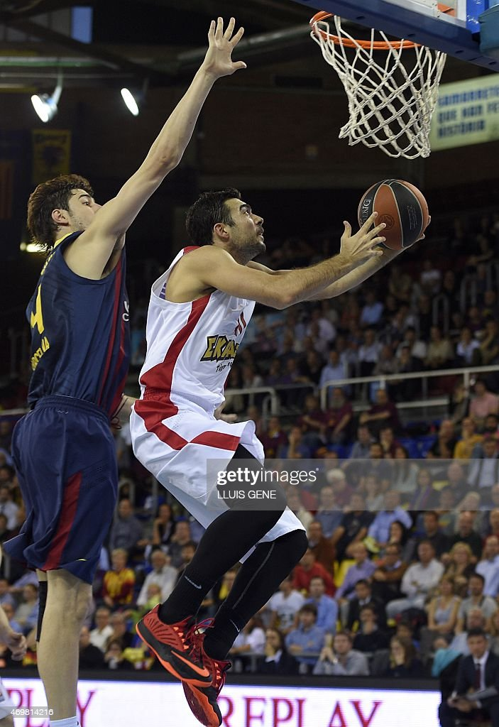 Olympiacos Piraeus' guard Kostas Sloukas (R) vies with Barcelona's Croatian centre Ante Tomic (L) during the Euroleague playoff basketball match FC Barcelona vs Olympiacos Piraeus at the Palau Blaugrana in Barcelona on April 15, 2015. AFP PHOTO / LLUIS GENE