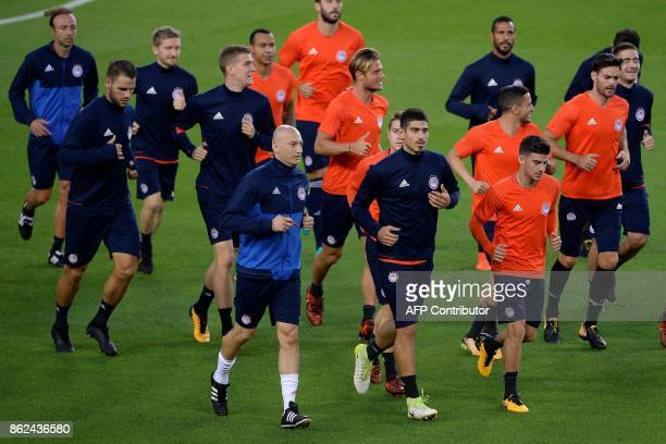 Olympiacos' players run during a training session at the camp nou stadium in Barcelona on October 17 2017 on the eve of the UEFA Champions League...
