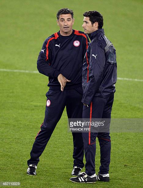Olympiacos' Spanish coach Michel chats with assistant coach Victor Sanchez del Amo during a training session at the Parc des Princes stadium in Paris...