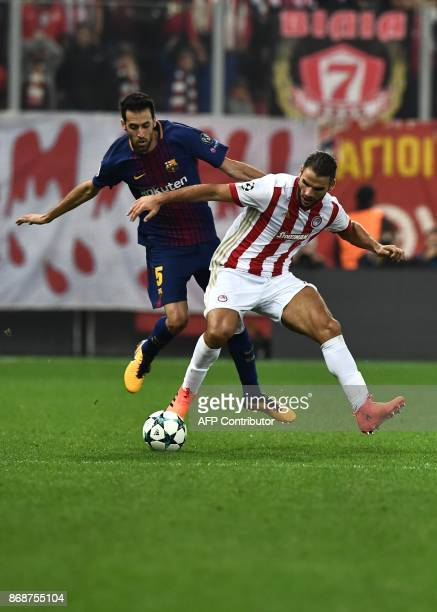 Olympiakos' Belgian defender Guillaume Gillet vies with Barcelona's Spanish midfielder Sergio Busquets during the UEFA Champions League group D...