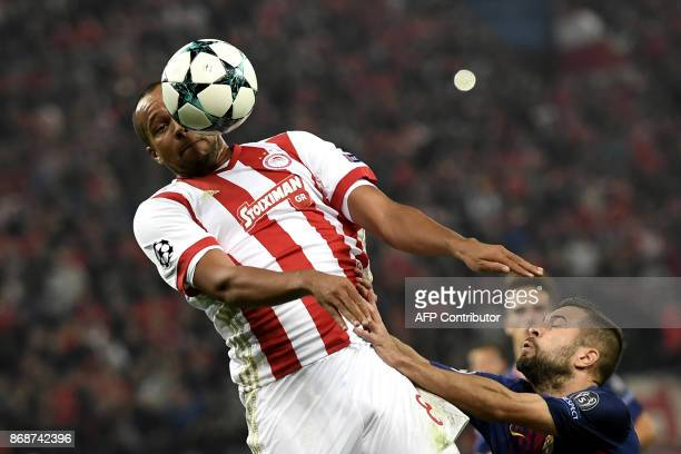Olympiakos' Belgian midfielder Vadis Odjida Ofoe heads the ball as he vies with Barcelona's Spanish midfielder Andres Iniesta during the UEFA...
