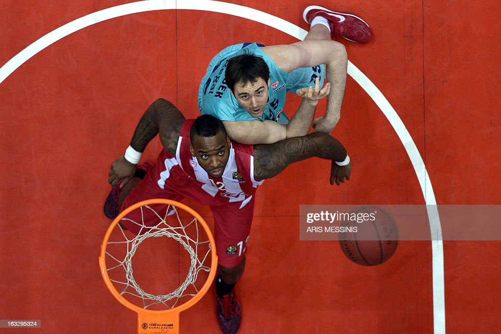 Olympiakos' Josh Powell (L) fights for a rebound with Barcelona's Erazem Lorbec during the Euroleague top 16 basketball match Olympiakos vs Barcelona in Athens on March 7, 2013. AFP PHOTO / ARIS MESSINIS