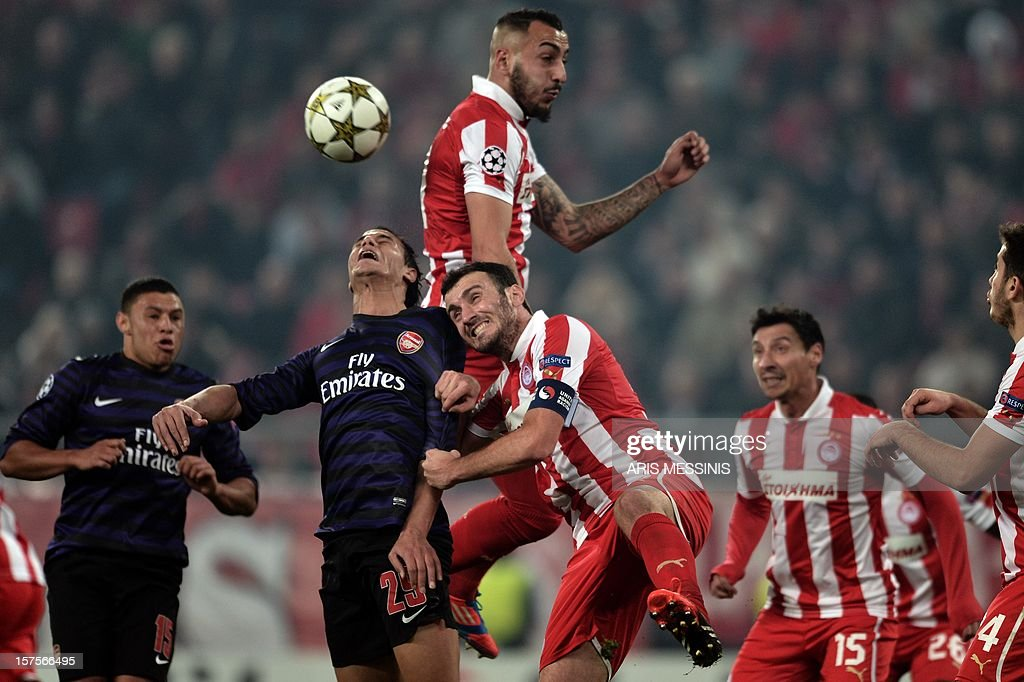 Olympiakos' Kostas Mitroglou (top) and Vassilis Torosidis (C) fight for the ball with Arsenals's Marouane Chamakh during their group B Champions league football game at the Karaiskaki stadium in Athens on December 4, 2012.