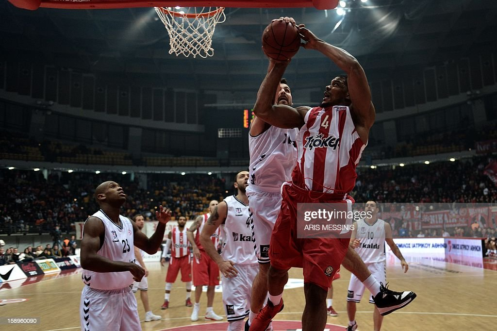 Olympiakos' Kyle Hines (R) jumps to score against Besiktas during their Euroleague top 16 basketball game in Athens on January 4, 2013.