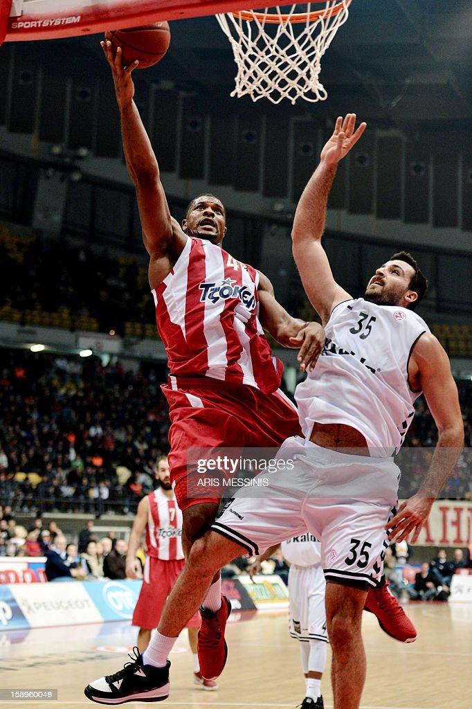 Olympiakos' Kyle Hines (L) jumps to score next to Besiktas' Nalga during an Euroleague top 16 basketball game in Athens on January 4, 2013.