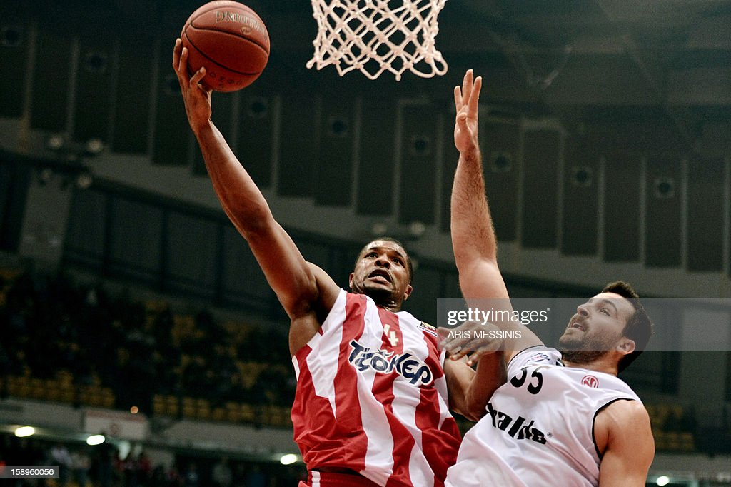 Olympiakos' Kyle Hines (L) jumps to score next to Besiktas' Nalga during an Euroleague top 16 basketball game in Athens on January 4, 2013. AFP PHOTO / ARIS MESSINIS