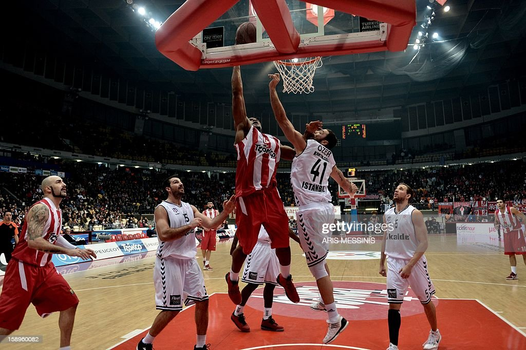 Olympiakos' Kyle Hines (C) jumps to score next to Cevher Ozer of Besiktas during their Euroleague top 16 basketball game in Athens on January 4, 2013. AFP PHOTO / ARIS MESSINIS