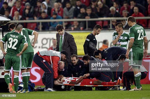 Olympiakos' Michael Olaitan is carried out from the field after being injured during the Greek Super League football match between Olympiakos and...