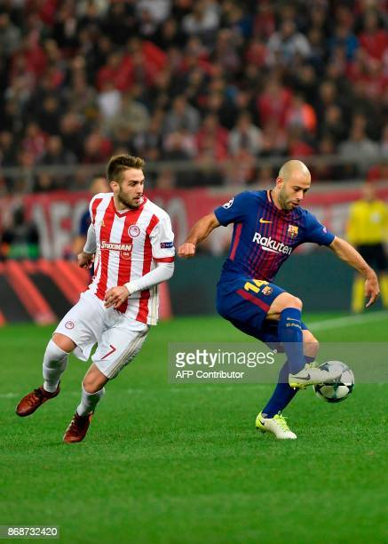 Olympiakos' midfielder Kostas Fortounis vies with Barcelona's Argentinian defender Javier Mascherano during the UEFA Champions League group D...