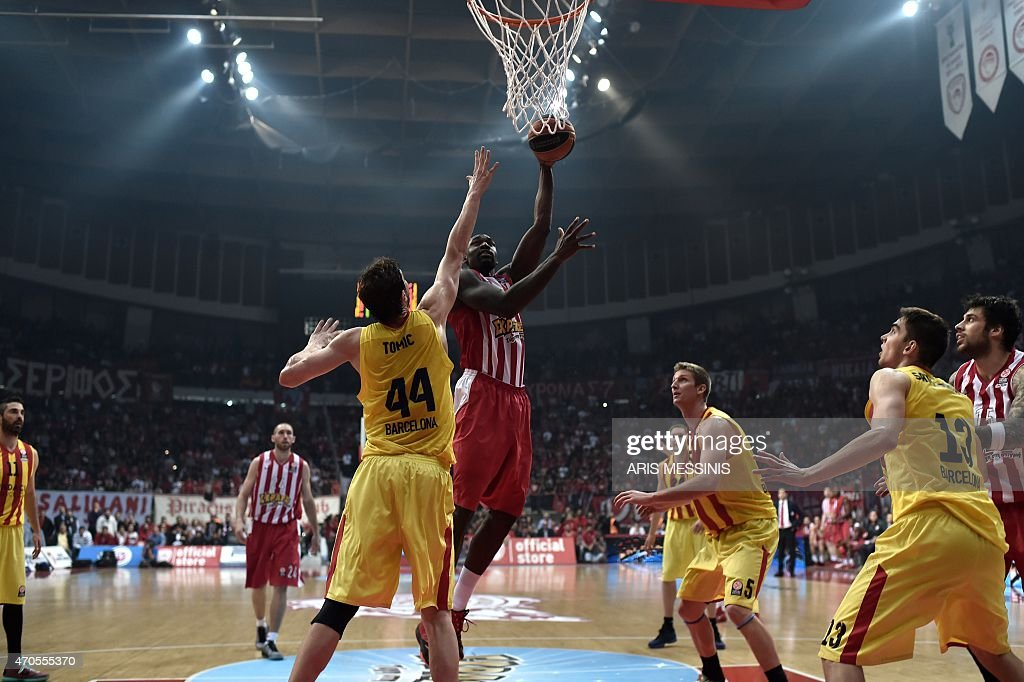 Olympiakos' <a gi-track='captionPersonalityLinkClicked' href=/galleries/search?phrase=Othello+Hunter&family=editorial&specificpeople=4100810 ng-click='$event.stopPropagation()'>Othello Hunter</a> (C) jumps to score between center Barcelona's Ante Tomic (2nd L) and power forward Justin Doellman (3rd R) during their round three play-off Euroleague basketball game at the Athens' Peace and Friendship stadium on April 21, 2015. AFP PHOTO / ARIS MESSINIS