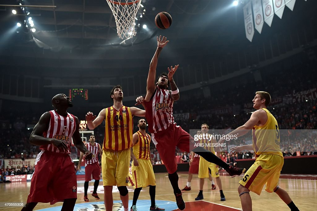 Olympiakos' power forward Giorgos Printezis (C) jumps to score between center Barcelona's Ante Tomic (2nd L) and power forward Justin Doellman (3rd L) during their round three play-off Euroleague basketball game at the Athens' Peace and Friendship stadium on April 21, 2015. AFP PHOTO / ARIS MESSINIS