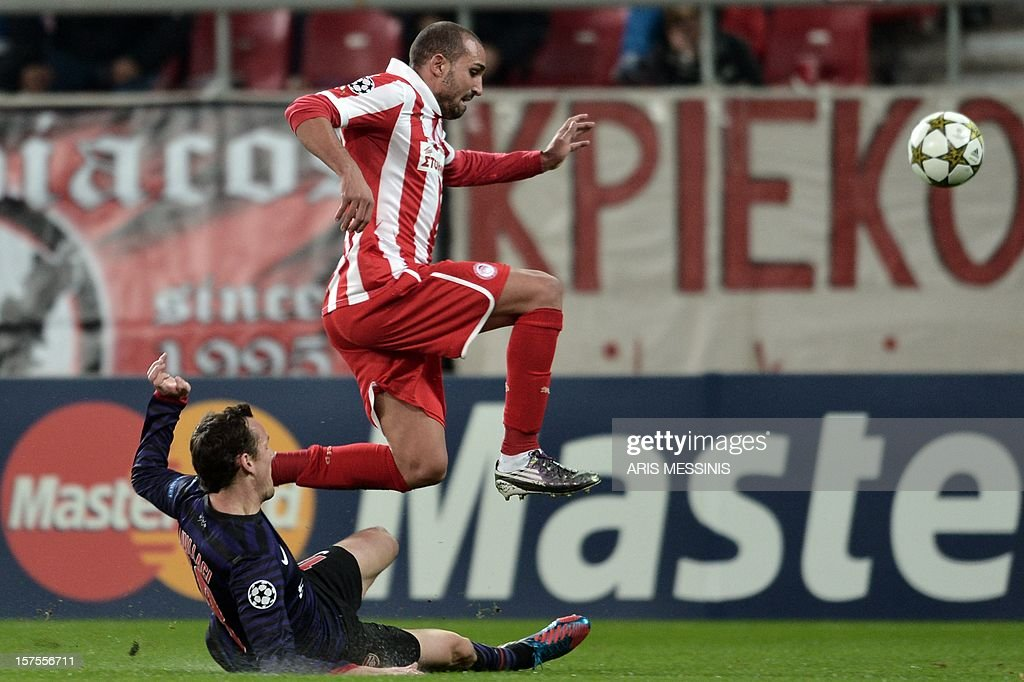 Olympiakos' Rafik Djebbour (top) fights for the ball with Arsenal's Sebastien Squillaci during their group B Champions league football match at the Karaiskaki stadium in Athens on December 4, 2012.