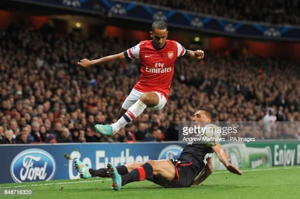 Olympiakos'Jose Holebas slides in on Arsenal's Theo Walcott