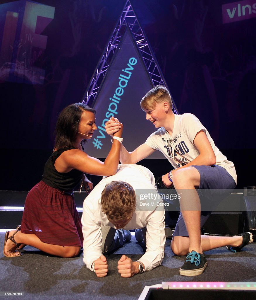 Olympian Zoe Smith (L) arm wrestles a member of the audience on Rick Edwards back at vInspired Live, a youth social change event, at The Roundhouse on July 6, 2013 in London, England.