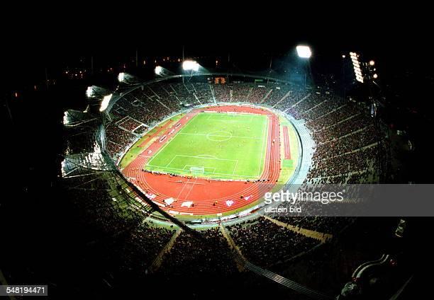 Übersichtsaufnahme aus erhöhter Perspektive von einem Kran über das Dach des Stadions in das mit Flutlicht beleuchtete und mit Zuschauern gefüllte...