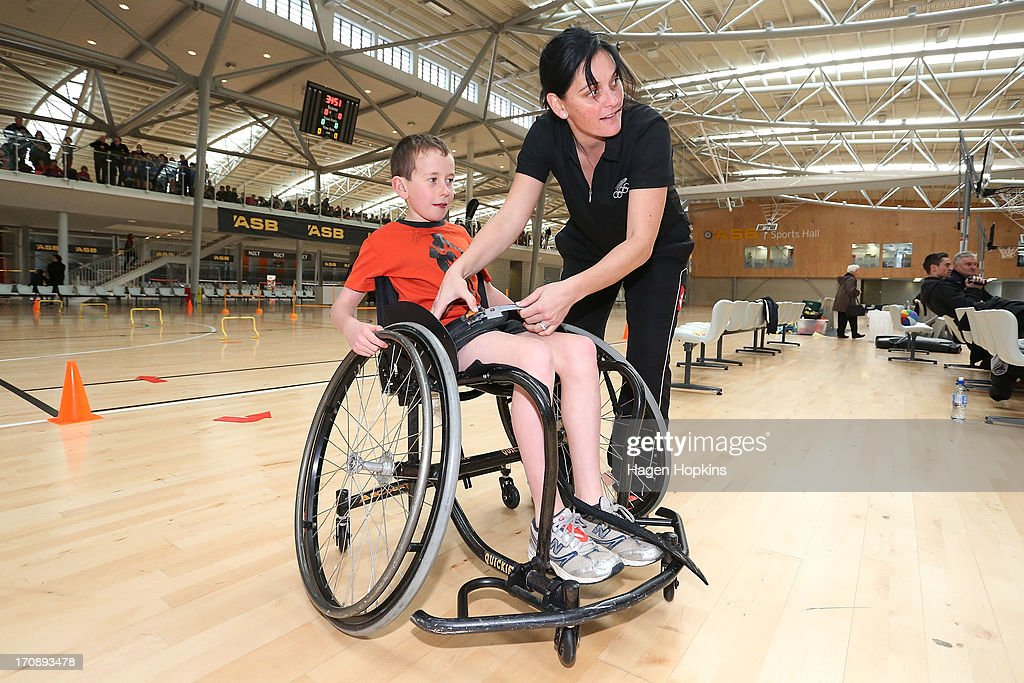 Olympic Ambassador Niniwa Roberts helps a child into a wheelchair for a game of wheelchair basketball during the launch of the New Zealand Olympic Ambassador Programme at ASB Sports Centre on June 20, 2013 in Wellington, New Zealand.