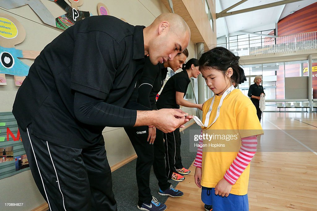 Olympic Ambassador Paora Winitana presents a child with a medal during the launch of the New Zealand Olympic Ambassador Programme at ASB Sports Centre on June 20, 2013 in Wellington, New Zealand.