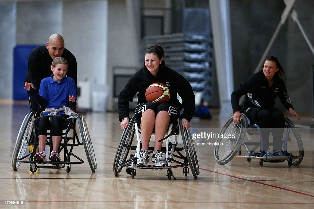 Olympic Ambassador Paora Winitana pushes a child while Suzie Bates (R) looks on during a game of wheelchair basketball at the launch of the New Zealand Olympic Ambassador Programme at ASB Sports Centre on June 20, 2013 in Wellington, New Zealand.