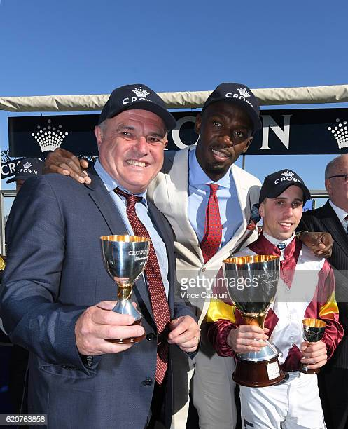 Olympic and world champion sprinter Usain Bolt poses at the trophy presentation with winning jockey Brenton Avdulla and Trainer Lee Curtis after...