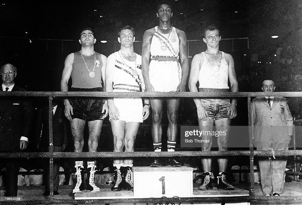 Olympic Games Rome Italy Boxing Light Heavyweight USA's gold medallist Cassius Clay stands on the podium with Polish silver medallist Piertzykowski...