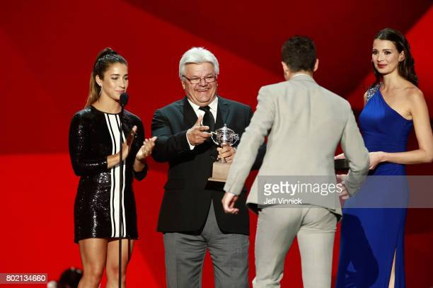 Olympic gold medal gymnast Aly Raisman and former NHL player Marcel Dionne greet Johnny Gaudreau of the Calgary Flames onstage after Gaudreau won the...