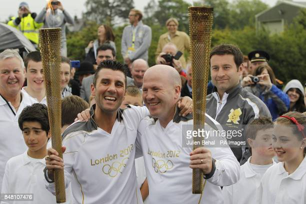 Olympic gold medal winning boxer Michael Carruth receives the flame from Olympic silver medal winner Wayne McCullough during the ceremony to hand...