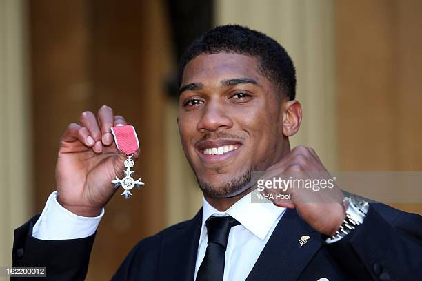 Olympic Gold Medalist Anthony Joshua proudly holds his Member of the British Empire medal after an the Investiture Ceremony at Buckingham Palace on...