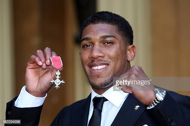Olympic Gold Medalist boxer Anthony Joshua holds his Member of the British Empire medal which he received at an Investiture Ceremony at Buckingham...