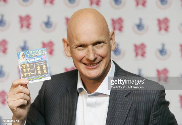 Olympic Gold Medalist Duncan Goodhew holds an Olympic Champions scratchcard at the launch in Piccadilly London