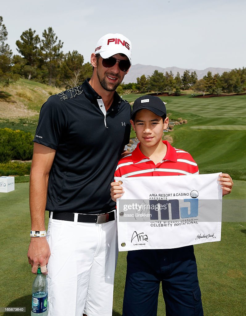 Olympic Gold Medalist Michael Phelps poses with Make-A-Wish child Joseph Domingues during ARIA Resort & Casino's Michael Jordan Celebrity Invitational golf tournament at Shadow Creek on April 6, 2013 in North Las Vegas, Nevada.