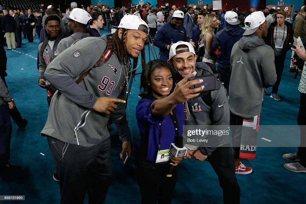 US Olympic gold medalist Simone Biles takes a selfie with Jabaal Sheard #93 and Tyler Gaffney #35 of the New England Patriots during Super Bowl 51 Opening Night at Minute Maid Park on January 30, 2017 in Houston, Texas.