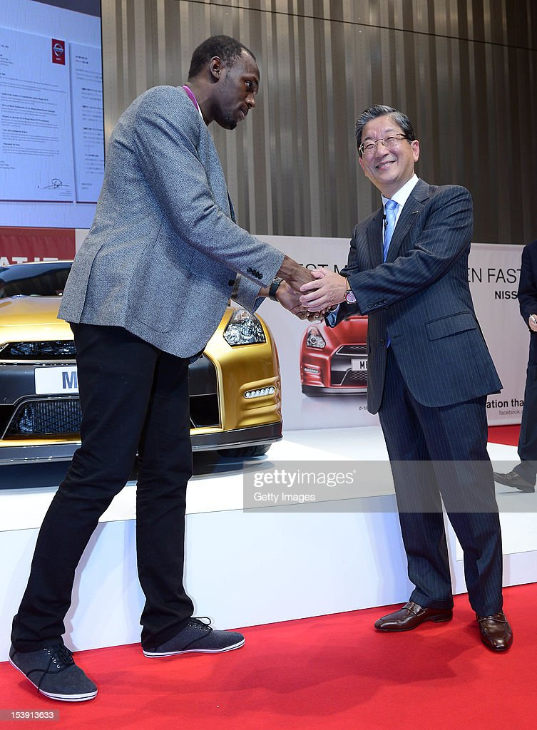 Olympic gold medalist Usain Bolt and Nissan Motor Co COO Toshiyuki Shiga shake hands during the Nissan GTR promotional event at the Nissan Motor Co...