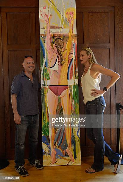 Olympic Gold Medalist Vollyballer Kerri Walsh and artist Les Rogers stands with a painting of Kerri titled 'Six Feet of Sunshine's' on June 19 2012...